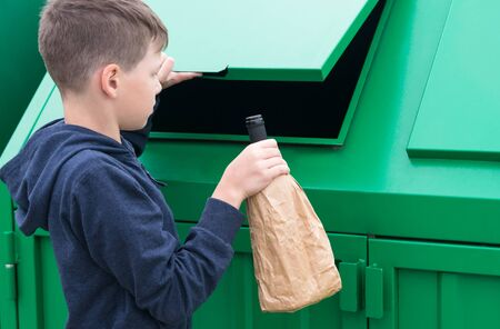 boy throws a bottle in a paper bag into a trash tank Stockfoto