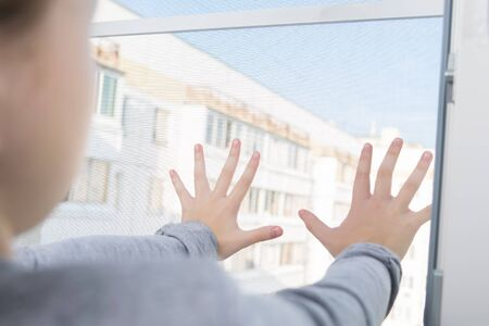 the girl dangerously put her hands in the open window on the mosquito net, an accident with children left alone at home Stockfoto