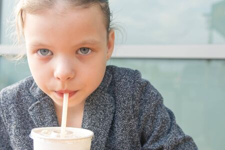 girl drinks milkshake through the straws front view close-up Stockfoto