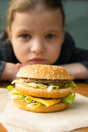 girl looking at a big tasty burger from far away, front view Stockfoto - 134207939