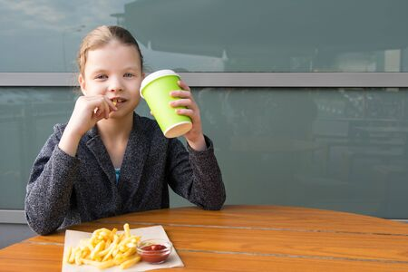 girl having lunch with junk food in a restaurant Stockfoto - 134207945