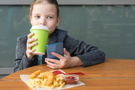 little girl eats delicious crispy fries and drinks tea from a paper cup Stockfoto - 134207950