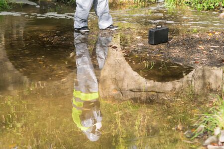 reflection in water of an employee in a protective suit of an environmental research company after technological disasters Stockfoto
