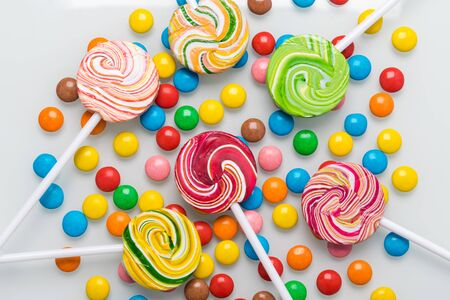 many chocolate and caramel candies of different tastes and colors lie on a light background