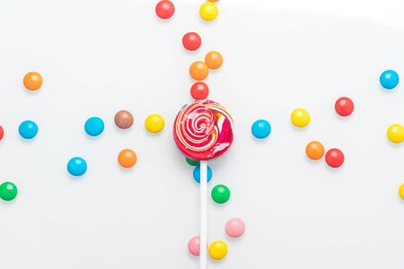 multi-colored chocolate dragee lies in the form of a cross on a light background Stockfoto - 134208133