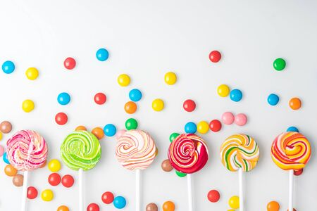 multi-colored chocolate tablets and caramel candies on a stick lie beautifully on a light background, top view