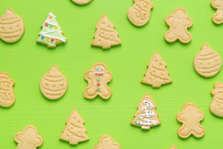 background of christmas cookies on a green table, top view