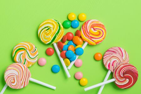 many multi-colored caramel candies on a stick lie on a green background Stockfoto