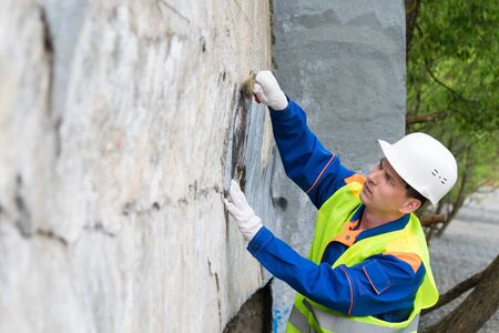a worker in a helmet cleans vandal inscriptions from the walls in the city