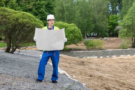 worker checks the construction plan on a large sheet of paper, control of work performed