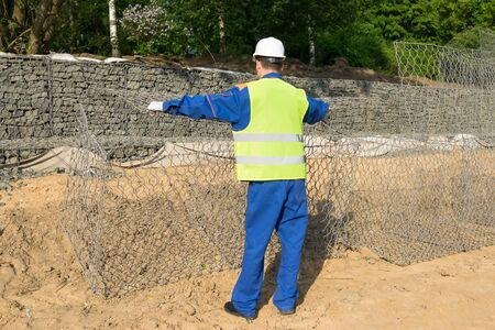 a worker spreads a protective net to strengthen the soil with gloves and a helmet