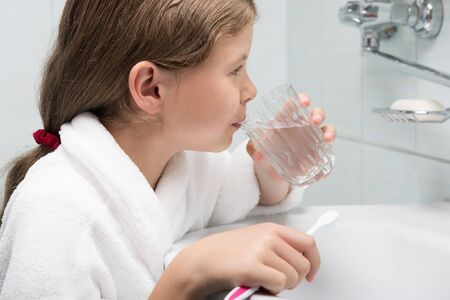 girl holding a glass of water in the bathroom, brushing her teeth
