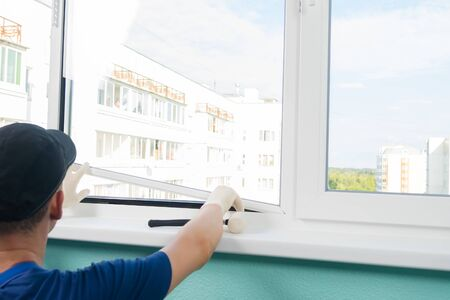 a window repairman fixes the glass to the frame with a glazing bead and a hammer Banco de Imagens