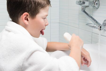 a boy in a white coat wants to wash his tongue with soap