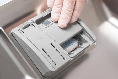 a gloved hand puts a chemical detergent in the door of the dishwasher