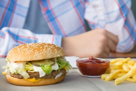 tasty juicy burger and potatoes with ketchup close-up on a background of hands Stockfoto