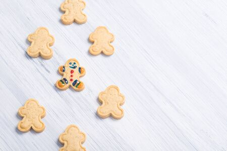 little men from cookies lie on a gray background on the right, place for an inscription on the left