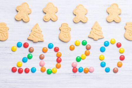gingerbread cookies of different shapes and in the middle the inscription 2020 from multi-colored dragees on a gray background