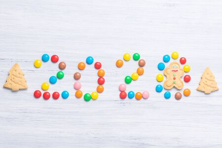 inscription 2020 made of multicolored round candies on a gray background, close-up