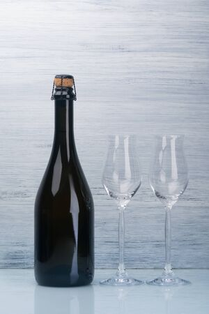 champagne bottle and two empty glasses on a gray background
