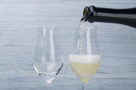 champagne is pouring from a bottle into a glass, closeup view