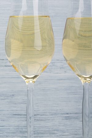 two full glasses with sparkling wine on a gray background