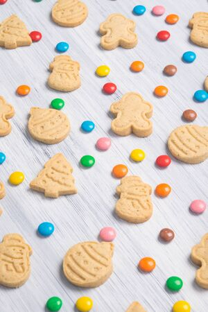 on a light gray table, laid out Christmas sweet cookies and colorful jelly beans