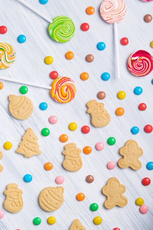 on a light gray table, laid out Christmas sweet cookies, colorful lollipops and jelly beans