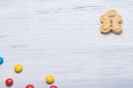 on a light gray background, cookies in the form of a snowman with icing and colorful dragees, in the middle there is a place for the inscription