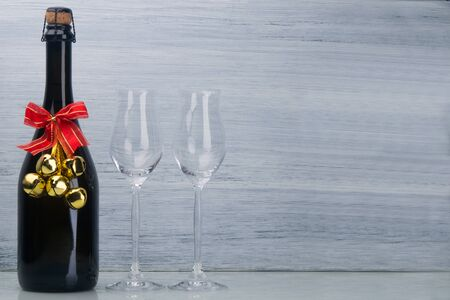 champagne alcoholic drink, in a black bottle with Christmas decoration, next to two glass glasses, on a light gray background, there is a place for inscription Stockfoto