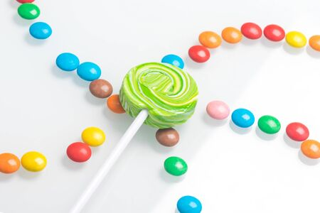on a multi-colored chocolate dragee lies caramel on a stick, a beautiful background