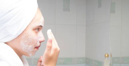 a girl with a towel on her head and a white coat, washes foam off her face, in the bathroom, near the mirror