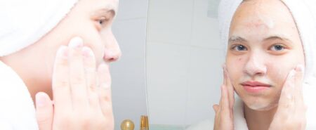 girl with a white towel on her head, washes foam off her face, in the bathroom, near the mirror, close-up Stockfoto