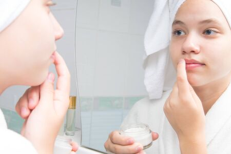 a girl with a white towel on her head and in a bathrobe, in the bathroom, near the mirror, puts cream on her lips to soften