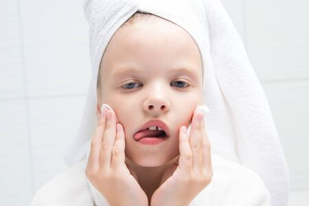 baby girl, with a white towel on her head, fooling around, cleaning her face with a round cotton swab, close-up, against the wall in the bathroom