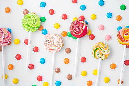 multicolored sweet lollipops, neatly laid out and round dragees, on a white background