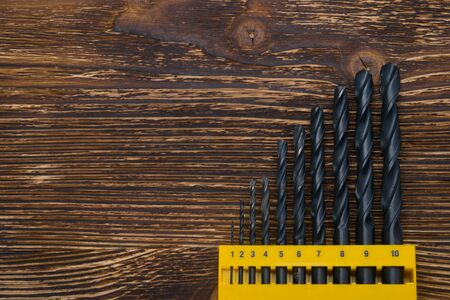 on a dark background, in a yellow stand, a set of drills on wood, there is a place for inscription