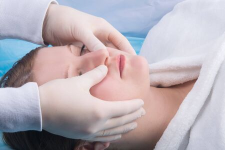 woman, in a white coat, doing facial massage at Spa treatments, close-up