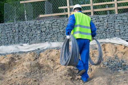 a worker in a blue uniform and a yellow vest, carries two skeins of metal wire, for further work