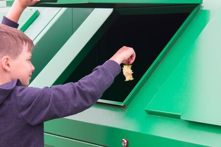 a boy in a blue jumper throws an Apple stub into a green dumpster Stockfoto