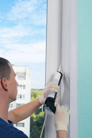 master in protective gloves, fills the cracks with silicone to seal the installation of a plastic window Stockfoto