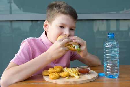 boy sitting at a table eating fast food and drinking water, close-up Stockfoto