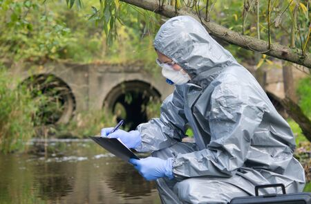 specialist, in a protective suit, mask and gloves, working with toxic substances, records the results of a sample of liquid from the river, on a sheet on a tablet