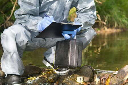 the specialist, in a protective suit and with a suitcase in his hand, is recording the findings at the crime scene on the pond