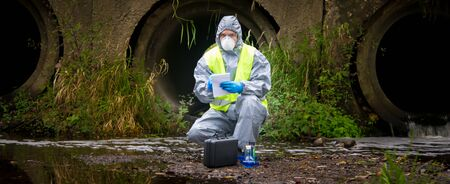 the scientist, wearing a protective suit, gloves and mask, took the liquid from the river, in test tubes, and writes the results in a notebook, against the drainpipes