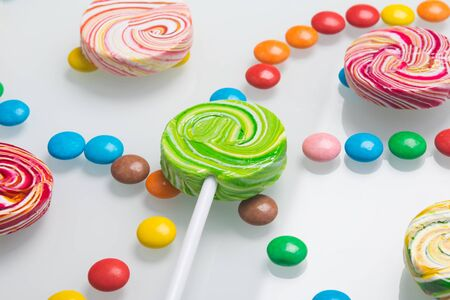 confectionery, close-up, colorful lollipops on a stick and neatly arranged dragees, on a white background Stockfoto