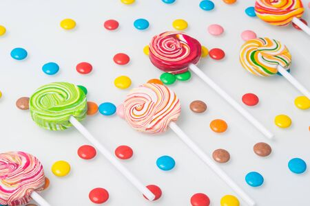 multi-colored lollipops, neatly arranged and round sweet dragees, on a white background Stockfoto