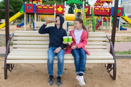 a girl offers a teenage boy tea in a glass, instead of an alcoholic drink, sitting on a Playground bench