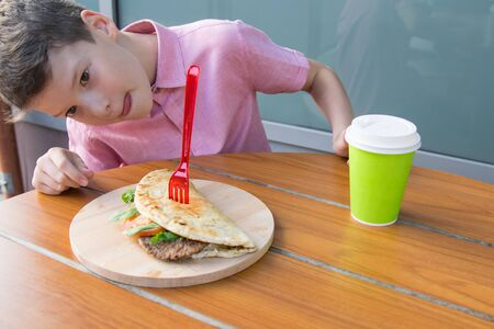 the boy sits at the table and looks at the Burger with appetite Stockfoto