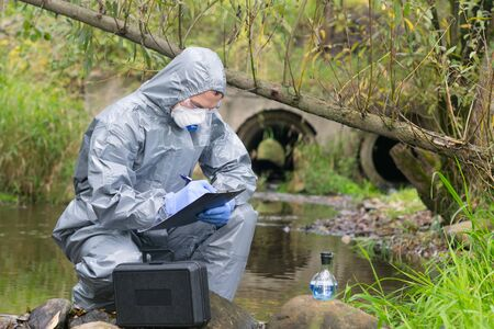 a specialist, in a protective suit and gloves, working with toxic substances, records the results of a sample of liquid from the river, on a sheet on a tablet, against the background of cleaning pipes